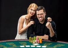 Les jeunes couples jouant le tisonnier profitent d'un agréable moment dans le casino Images stock