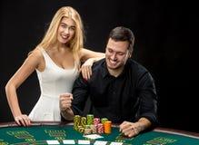 Les jeunes couples jouant le tisonnier profitent d'un agréable moment dans le casino Photos libres de droits