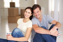Les jeunes couples juste ont déménagé dedans à la maison neuve Image stock