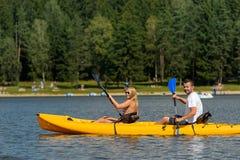 Sur de jeunes couples d'étang se reposant dans le kayak Photos stock