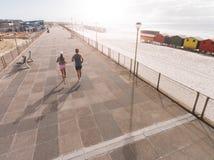 Les jeunes couples le matin fonctionnent à la promenade de plage Images stock
