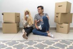 Les jeunes couples malais font une pause apr?s le d?placement de maison photos stock
