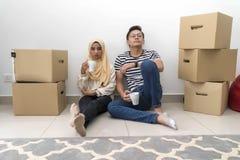 Les jeunes couples malais font une pause apr?s le d?placement de maison image libre de droits