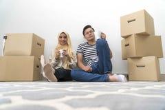 Les jeunes couples malais font une pause apr?s le d?placement de maison images libres de droits