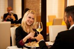Les jeunes couples mangent le dîner de fruits de mer au restaurant et boivent du vin Photo libre de droits