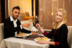 Les jeunes couples mangent le dîner de fruits de mer au restaurant et boivent du vin Photos libres de droits