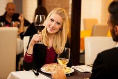 Les jeunes couples mangent le dîner de fruits de mer au restaurant et boivent du vin Image libre de droits