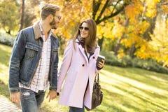 Les jeunes couples marchant avec des tasses de café pendant l'automne se garent Photographie stock libre de droits