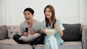 Les jeunes couples mettent en oeuvre à la télévision de observation et emploient à télécommande Photo stock