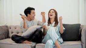 Les jeunes couples mettent en oeuvre à la télévision de observation et emploient à télécommande Photos libres de droits