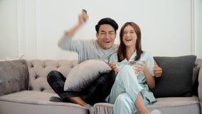 Les jeunes couples mettent en oeuvre à la télévision de observation et emploient à télécommande Image stock