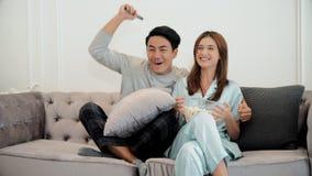 Les jeunes couples mettent en oeuvre à la télévision de observation et emploient à télécommande Photographie stock