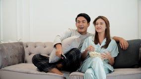 Les jeunes couples mettent en oeuvre à la télévision de observation et emploient à télécommande Photo libre de droits