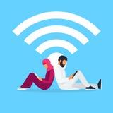 Les jeunes couples musulmans se reposent de nouveau au dos et lisent utilisant un PC de comprimé Image stock