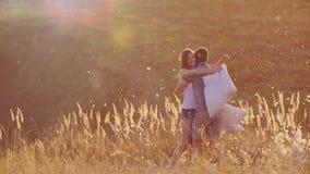 Les jeunes couples ont follement l'amusement Une femme bat son oreiller avec un ami, plumes volent Combat contre banque de vidéos