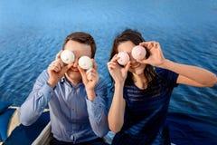 Les jeunes couples ont l'amusement avec des gâteaux près de l'eau images stock