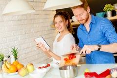 Les jeunes couples ont l'amusement dans la cuisine moderne d'intérieur tout en préparant v Photo libre de droits