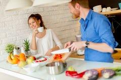 Les jeunes couples ont l'amusement dans la cuisine moderne d'intérieur tout en préparant v Image libre de droits