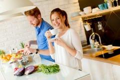Les jeunes couples ont l'amusement dans la cuisine moderne d'intérieur tout en préparant v Photos libres de droits