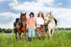 Les jeunes couples ont plaisir à marcher avec des chevaux dans un domaine Images libres de droits