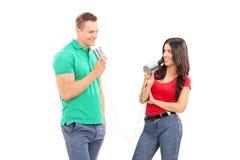 Les jeunes couples parlant par une boîte en fer blanc téléphonent Photographie stock libre de droits