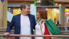 Les jeunes couples parlent et ont l'amusement avec des paquets des achats au centre commercial Le couple sourit avec les paquets  clips vidéos