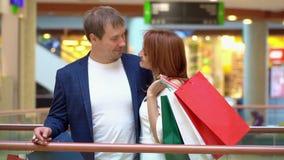 Les jeunes couples parlent et ont l'amusement avec des paquets des achats au centre commercial Le couple sourit avec les paquets  banque de vidéos