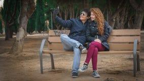 Les jeunes couples passent le temps en parc et prennent des selfies photos libres de droits