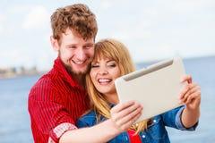 Les jeunes couples prenant l'individu décrivent le selfie avec le comprimé Photo stock