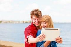 Les jeunes couples prenant l'individu décrivent le selfie avec le comprimé Photos stock