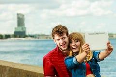 Les jeunes couples prenant l'individu décrivent le selfie avec le comprimé Image stock