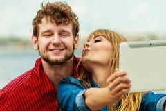 Les jeunes couples prenant l'individu décrivent le selfie avec le comprimé Photo libre de droits