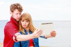Les jeunes couples prenant l'individu décrivent le selfie avec le comprimé Images stock
