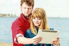 Les jeunes couples prenant l'individu décrivent le selfie avec le comprimé Photos libres de droits