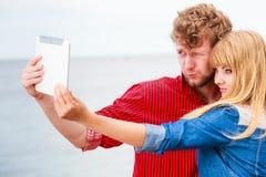 Les jeunes couples prenant l'individu décrivent le selfie avec le comprimé Photographie stock libre de droits
