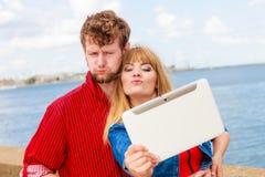 Les jeunes couples prenant l'individu décrivent le selfie avec le comprimé Image libre de droits