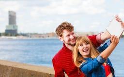 Les jeunes couples prenant l'individu décrivent le selfie avec le comprimé Images libres de droits