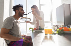 Les jeunes couples prenant le petit déjeuner, homme hispanique mangent la femme asiatique faisant cuire la cuisine de nourriture Photos stock