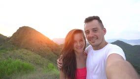 Les jeunes couples prenant le selfie, riant et s'attaquent en rond dans les montagnes avec la belle vue aérienne de ville au couc Image stock