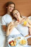 Les jeunes couples prennent le petit déjeuner dans le bâti Photographie stock