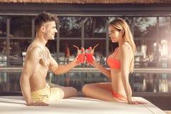 Les jeunes couples reposent le mode de vie sain togethernear de piscine Images libres de droits