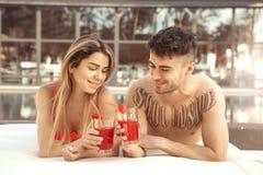 Les jeunes couples reposent le mode de vie sain togethernear de piscine Photographie stock libre de droits