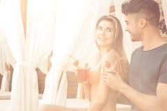 Les jeunes couples reposent le mode de vie sain togethernear de piscine Photo stock