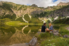 Les jeunes couples riant et ayant l'amusement devant un lac/couple de montagne se tenant en belle nature aménagent en parc de Bav photo stock