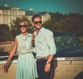 Les jeunes couples riches s'approchent du convertible classique contre le palais royal Image stock