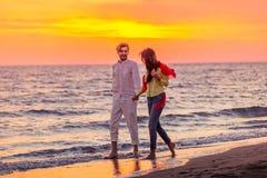 Les jeunes couples romantiques heureux dans l'amour ont l'amusement sur la belle plage au beau jour d'été Photographie stock libre de droits