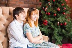 Les jeunes couples romantiques s'approchent de l'arbre de Noël Images stock