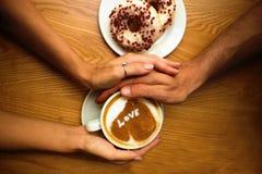 Les jeunes couples romantiques se reposent en café, mains de plan rapproché tenant une tasse de café avec le coeur là-dessus et 2 image stock
