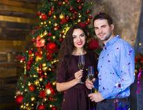 Les jeunes couples s'approchent de la cheminée célébrant Noël Photographie stock