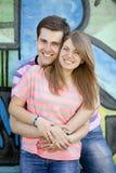 Les jeunes couples s'approchent du fond de graffiti. Photo libre de droits